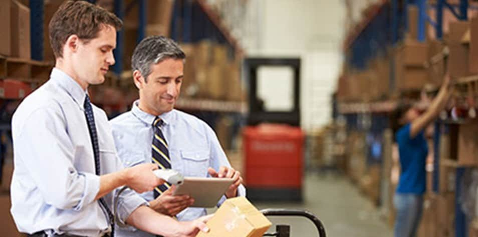 Two men using tablet in a warehouse